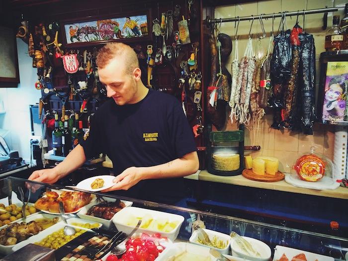 Ein Kellner mit Tapas in einer der Xampanyeria Barcelona