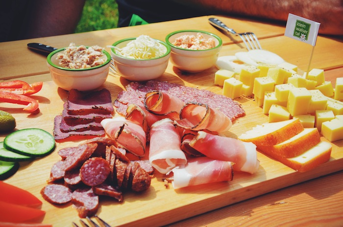 A piece of wood is covered with delicious food like sausages and cheese