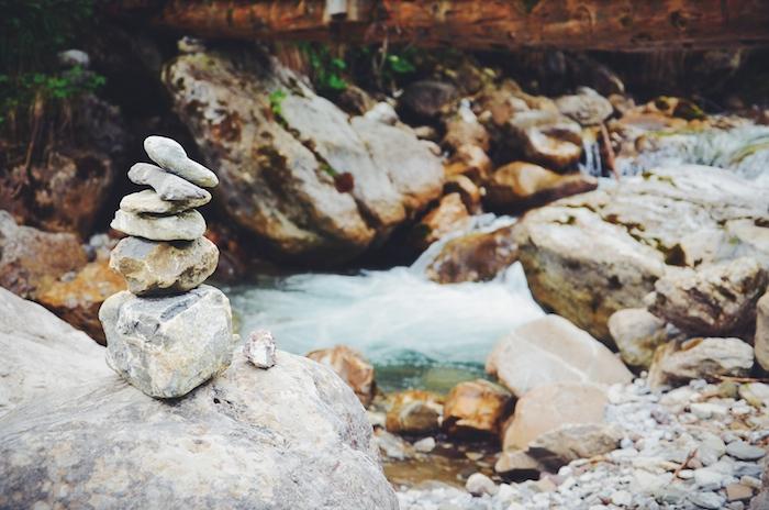 Aufeinander gestapelte Steine an einem Fluss im Kleinwalsertal