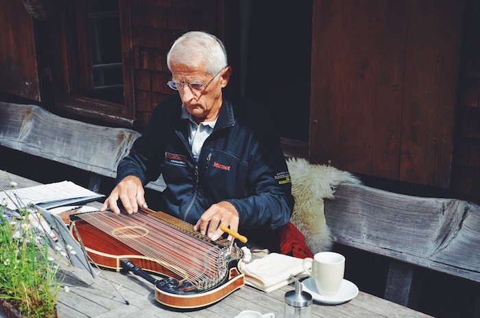 In the Kleinwalsertal an old man is playing the zither while sitting at a table
