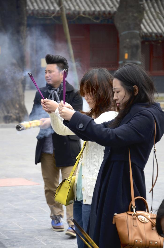 Nicht nur der Mönch betet im Lamatempel in Peking, sondern auch Besucher